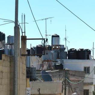 The water supply is severely restricted, so people store water in rooftop cisterns. Water flows freely in the ridgetop Israeli settlements behind the wall, formeting further resentment.